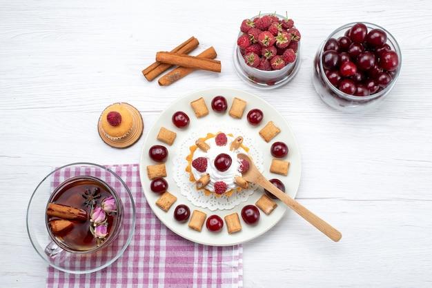 Draufsicht kleiner köstlicher kuchen mit himbeerkirschen und kleinen keksen tee zimt auf dem weißen tisch obst beeren sahne tee Kostenlose Fotos