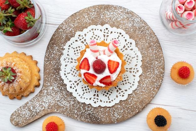 Draufsicht kleiner köstlicher kuchen mit sahne und geschnittenen roten frischen erdbeerkuchen auf dem weißen tischkuchenbeere süß backen obst backen Kostenlose Fotos