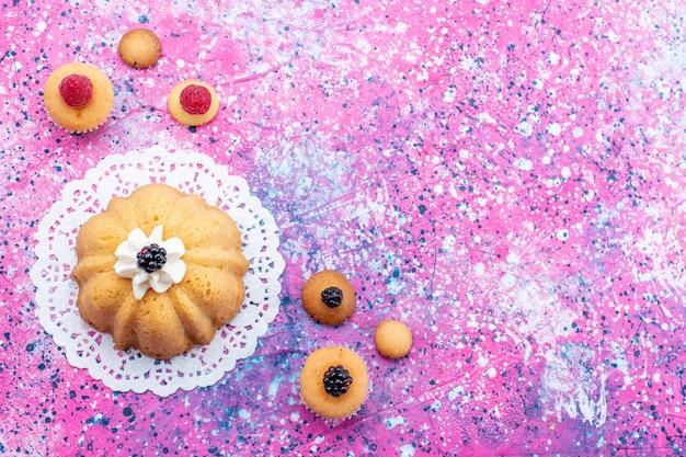 Draufsicht kleiner köstlicher kuchen mit sahne zusammen mit beeren auf dem hellen schreibtischkuchenplätzchenbeer-süßzuckerfoto Kostenlose Fotos