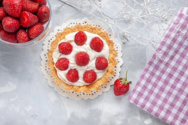 Draufsicht kleiner leckerer kuchen mit sahne und frischen roten erdbeeren auf der leichten schreibtischkuchen-fruchtkekscreme Kostenlose Fotos