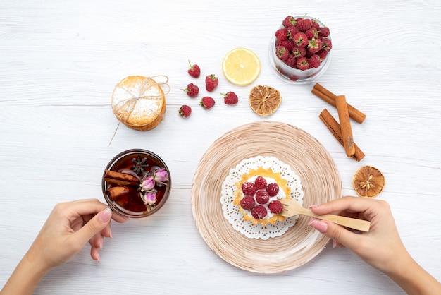 Draufsicht kleiner leckerer kuchen mit sahne und himbeeren zusammen mit sandwichkeksen zimttee auf dem hellen tisch obstbeerenkuchen keks süß Kostenlose Fotos