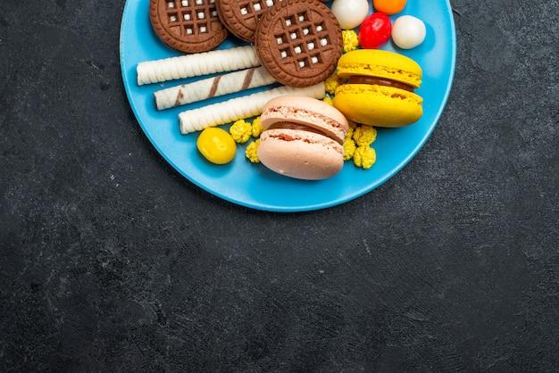 Draufsicht köstliche französische macarons mit bonbons und schokoladenplätzchen auf dunkelgrauem hintergrundkekszuckerkuchen süße backplätzchen Kostenlose Fotos