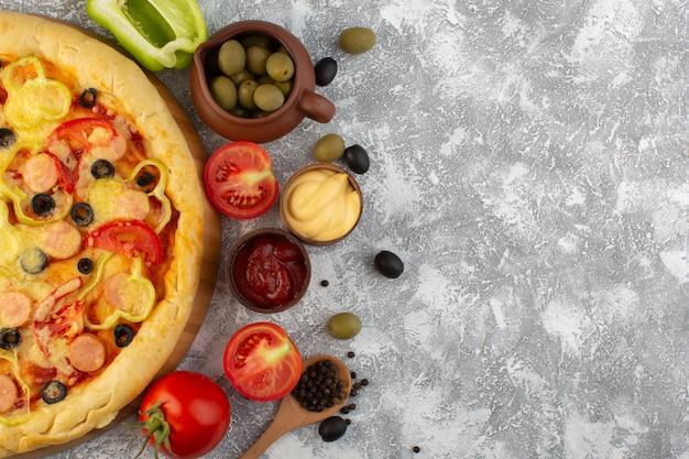 Draufsicht köstliche käsige pizza mit olivenwürsten und roten tomaten auf dem grauen hintergrund fast-food-italienischer teig Kostenlose Fotos