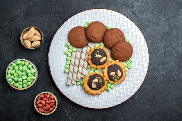 Draufsicht köstliche kekse mit verschiedenen bonbons auf dunkelgrauem hintergrundzuckerkeks süßer kuchen kuchen tee kekse Kostenlose Fotos