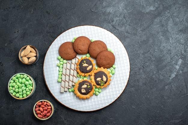 Draufsicht köstliche kekse mit verschiedenen süßigkeiten auf dunkelgrauem hintergrundzuckerkeks süßer kuchenkuchen-teekeks Kostenlose Fotos