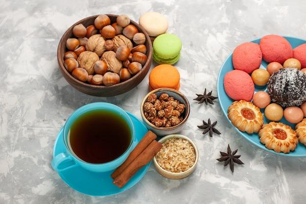 Draufsicht köstliche kuchen mit macarons nüssen tee und keksen auf der weißen oberfläche Kostenlose Fotos