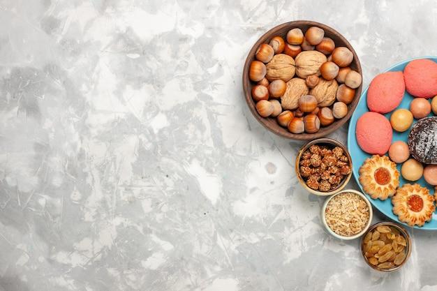 Draufsicht köstliche kuchen mit macarons nüssen und keksen auf dem weißen schreibtisch Kostenlose Fotos