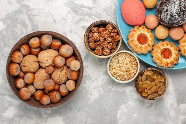 Draufsicht köstliche kuchen mit macarons nüssen und keksen auf der weißen oberfläche Kostenlose Fotos