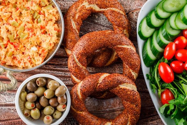 Draufsicht köstliche mahlzeit im teller mit türkischem bagel, salat, gurken in der schüssel auf holzoberfläche Kostenlose Fotos