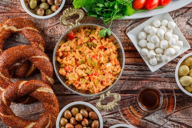 Draufsicht köstliche mahlzeit in teller mit türkischem bagel, einer tasse tee, salat, gurken auf holzoberfläche Kostenlose Fotos