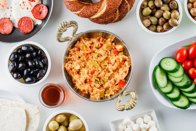Draufsicht köstliche mahlzeiten in der pfanne mit salat, gurken, türkischem bagel auf weißer oberfläche Kostenlose Fotos