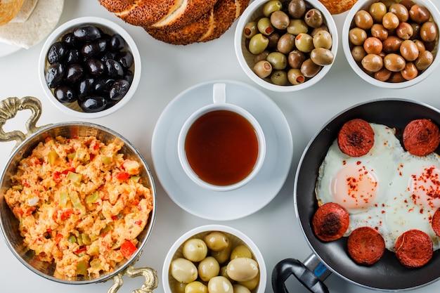 Draufsicht köstliche mahlzeiten in pfanne und kanne mit gurken, eine tasse tee auf weißer oberfläche Kostenlose Fotos