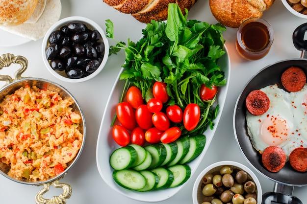 Draufsicht köstliche mahlzeiten in pfanne und kanne mit salat, gurken, türkischem bagel, einer tasse tee auf weißer oberfläche Kostenlose Fotos