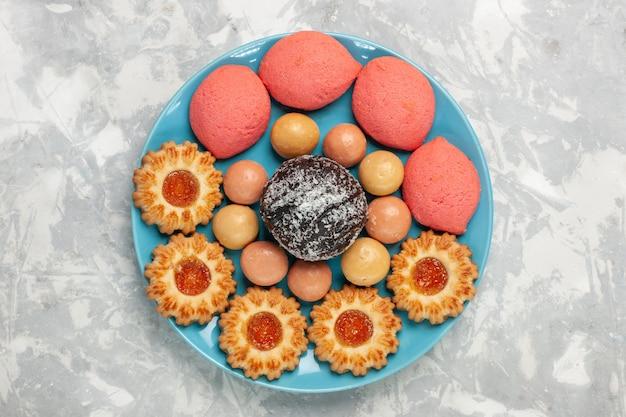 Draufsicht köstliche rosa kuchen mit keksen und schokoladenkuchen auf weißer oberfläche Kostenlose Fotos