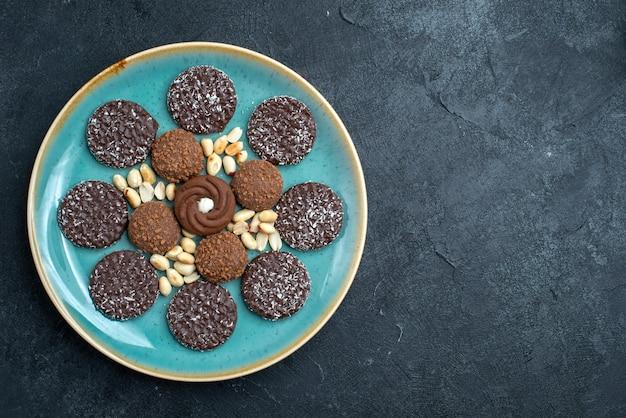 Draufsicht köstliche schokoladenkekse rund geformte innenplatte auf dunkelgrauem hintergrundkekszuckerkuchen süße torte-teekekse Kostenlose Fotos