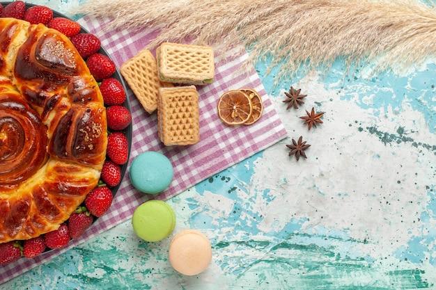 Draufsicht köstliche torte mit macarons waffeln und frischen roten erdbeeren auf blauer oberfläche Kostenlose Fotos