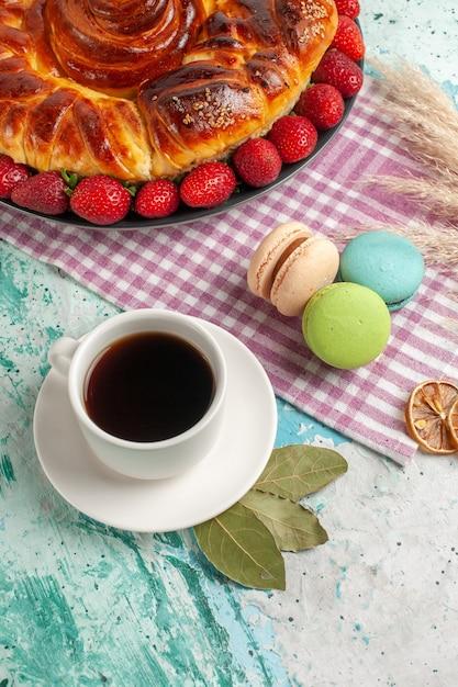 Draufsicht köstliche torte mit roten erdbeeren und tasse tee auf blauer oberfläche Kostenlose Fotos