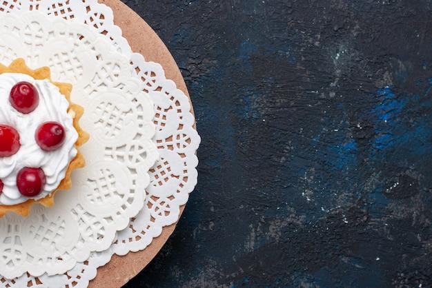 Draufsicht köstlicher d kuchen mit sahne und roten früchten auf dem dunklen oberflächenkuchenfruchtkeks Kostenlose Fotos