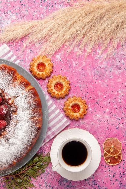 Draufsicht köstlicher erdbeerkuchenzucker pulverisiert mit keksen und tasse tee auf rosa oberflächenkuchen süßer zuckerkeksplätzchentee Kostenlose Fotos