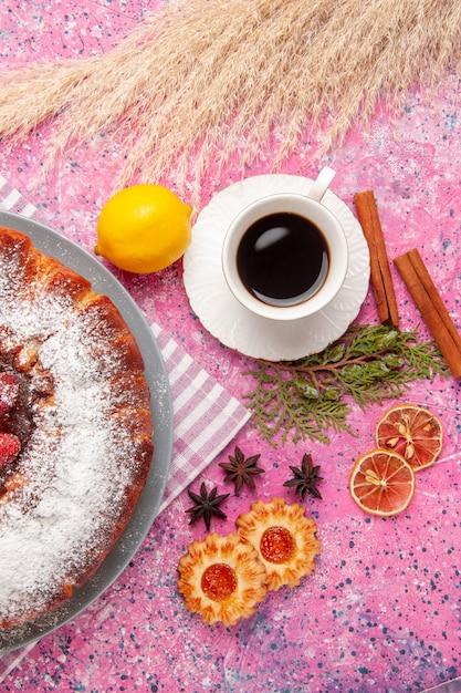 Draufsicht köstlicher erdbeerkuchenzucker pulverisiert mit keksen und tee auf rosa oberflächenkuchen süßer zuckerplätzchentee Kostenlose Fotos