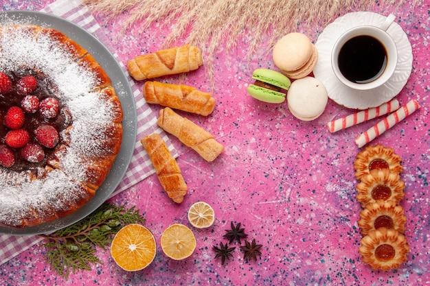 Draufsicht köstlicher erdbeerkuchenzucker pulverisiert mit tasse tee französische macarons und bagels auf rosa schreibtischkuchen süßer kekszuckerplätzchen Kostenlose Fotos