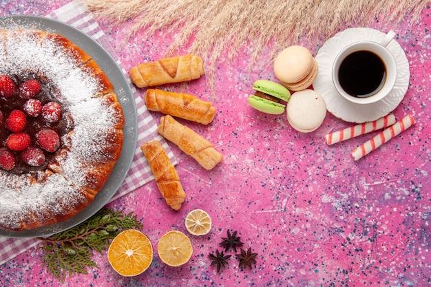 Draufsicht köstlicher erdbeerkuchenzucker pulverisiert mit tee macarons auf rosa hintergrundkuchen süßer keksplätzchentee Kostenlose Fotos