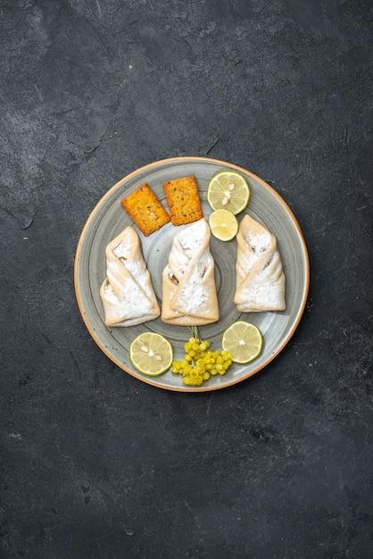 Draufsicht köstlicher teig mit zuckerpulver und crackern auf dunkelgrauem hintergrundgebäck backen zucker süßer kuchenplätzchen Kostenlose Fotos
