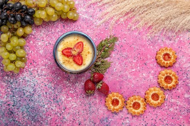 Draufsicht köstliches cremiges dessert mit frischen grünen trauben und keksen auf dem hellrosa hintergrunddessert eisbeerencreme süße frucht Kostenlose Fotos