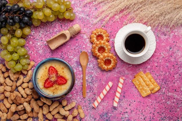 Draufsicht köstliches cremiges dessert mit frischen traubenplätzchen und erdnüssen auf der hellrosa oberfläche desserteis beerencreme süße frucht Kostenlose Fotos
