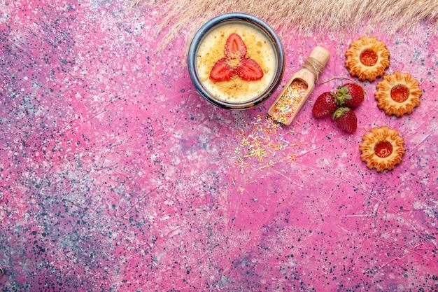 Draufsicht köstliches cremiges dessert mit rot geschnittenen erdbeeren und kleinen keksen auf hellrosa schreibtischdessert eisbeerencreme süße frucht Kostenlose Fotos