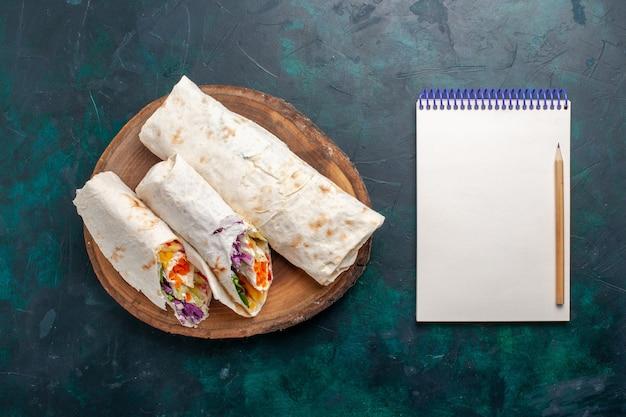 Draufsicht köstliches fleischsandwich ein sandwich aus fleisch, das auf einem spieß gegrillt wird, der auf dunkelblauem schreibtisch-sandwich-burger-essen-mahlzeit-mittagsfleisch geschnitten wird Kostenlose Fotos