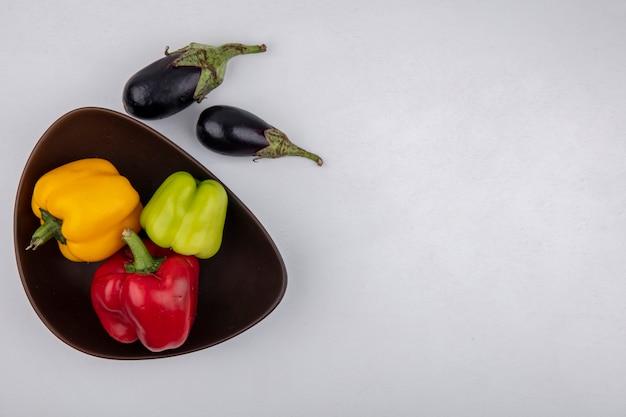 Draufsicht kopieren raum-aubergine mit farbigen paprika in der schüssel auf weißem hintergrund Kostenlose Fotos