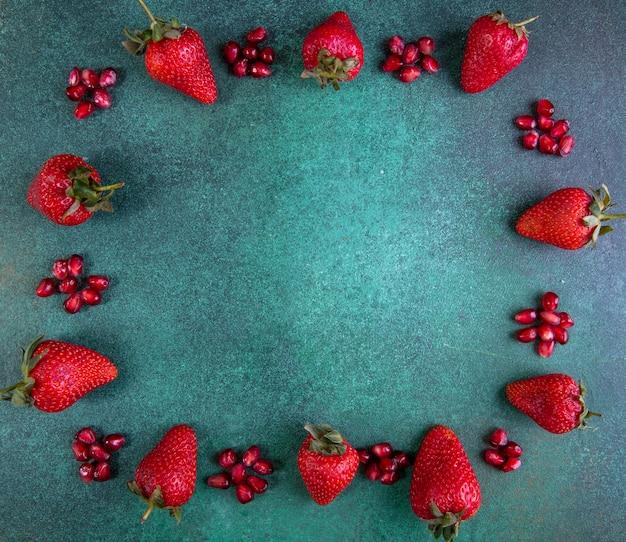 Draufsicht kopieren raum erdbeeren mit geschältem granatapfel an den rändern auf grün Kostenlose Fotos