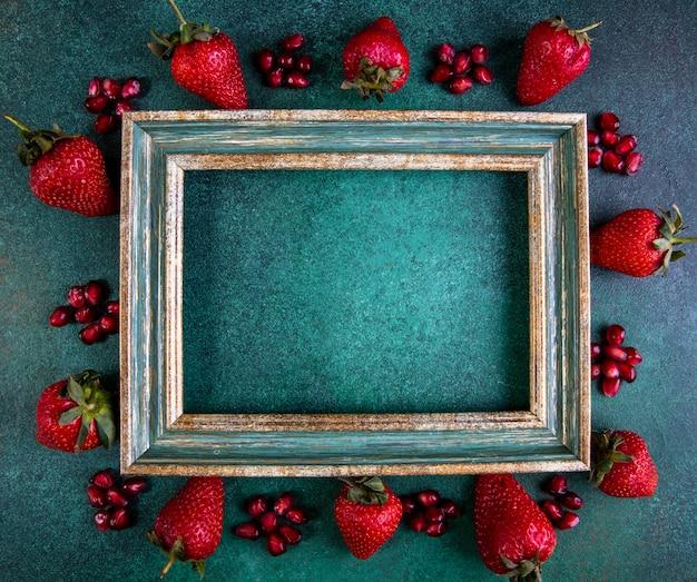 Draufsicht kopieren raum erdbeeren mit geschältem granatapfel um den rahmen auf grün Kostenlose Fotos