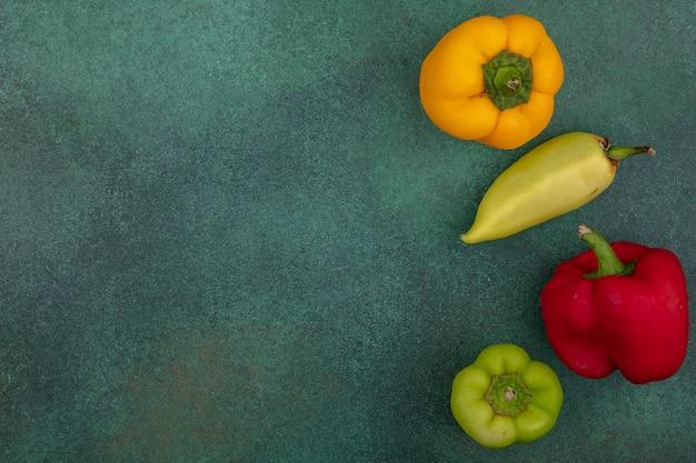 Draufsicht kopieren raum farbige paprika auf einem grünen hintergrund Kostenlose Fotos