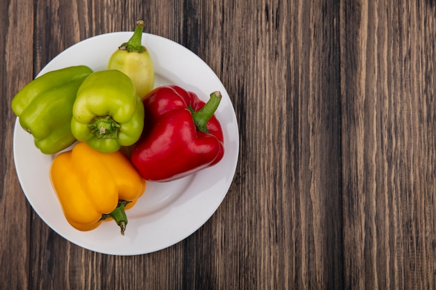 Draufsicht kopieren raum farbige paprika auf einem teller auf einem hölzernen hintergrund Kostenlose Fotos