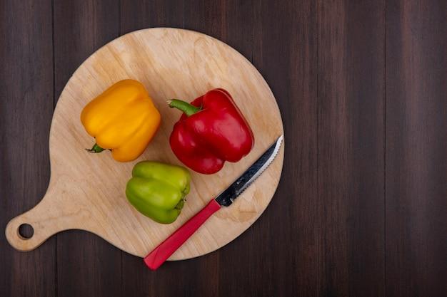 Draufsicht kopieren raum farbige paprika auf schneidebrett mit messer auf holzhintergrund Kostenlose Fotos