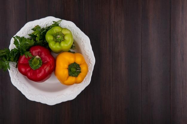 Draufsicht kopieren raum farbige paprika in platte mit petersilie auf hölzernem hintergrund Kostenlose Fotos