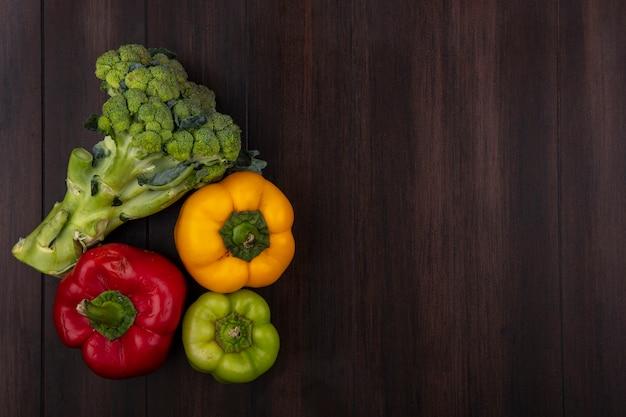 Draufsicht kopieren raum farbige paprika mit brokkoli auf hölzernem hintergrund Kostenlose Fotos