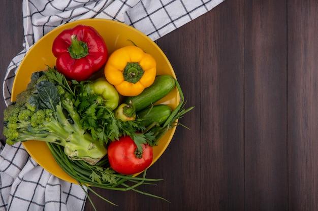 Draufsicht kopieren raum farbige paprika mit brokkoli-gurkentomate und frühlingszwiebeln auf gelbem teller auf hölzernem hintergrund Kostenlose Fotos