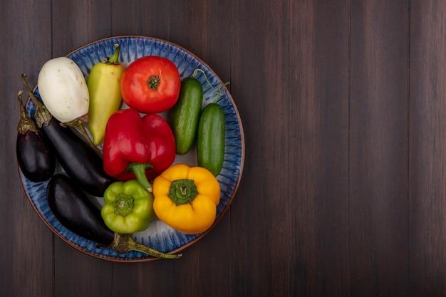 Draufsicht kopieren raum farbige paprika mit gurken und tomaten auberginen auf einem teller auf holzhintergrund Kostenlose Fotos