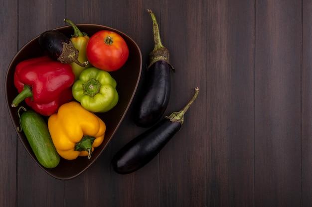 Draufsicht kopieren raum farbige paprika mit gurken und tomaten in schüssel mit auberginen auf hölzernem hintergrund Kostenlose Fotos