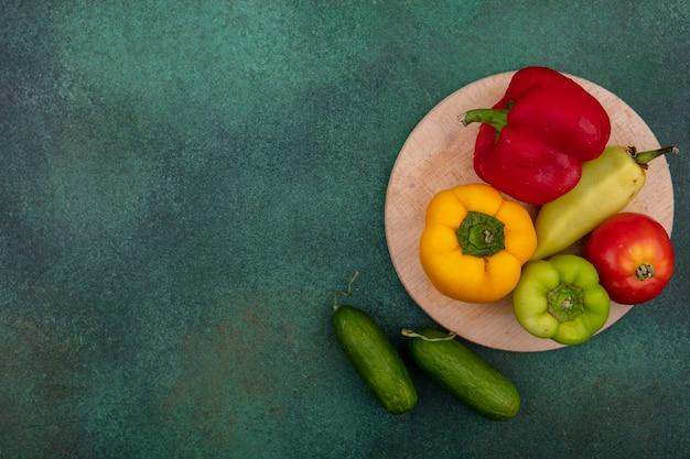 Draufsicht kopieren raum farbige paprika mit tomate auf ständer und gurken auf grünem hintergrund Kostenlose Fotos