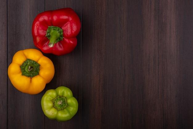 Draufsicht kopieren raum farbige paprika rot gelb und grün auf hölzernem hintergrund Kostenlose Fotos