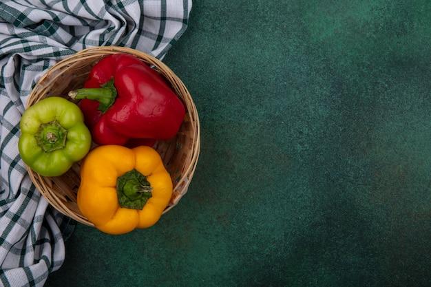Draufsicht kopieren raum-paprika in einem korb auf einem grünen hintergrund Kostenlose Fotos