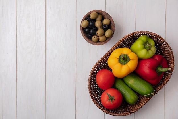 Draufsicht kopieren raum-paprika mit tomatengurken in einem korb mit oliven auf einem weißen hintergrund Kostenlose Fotos