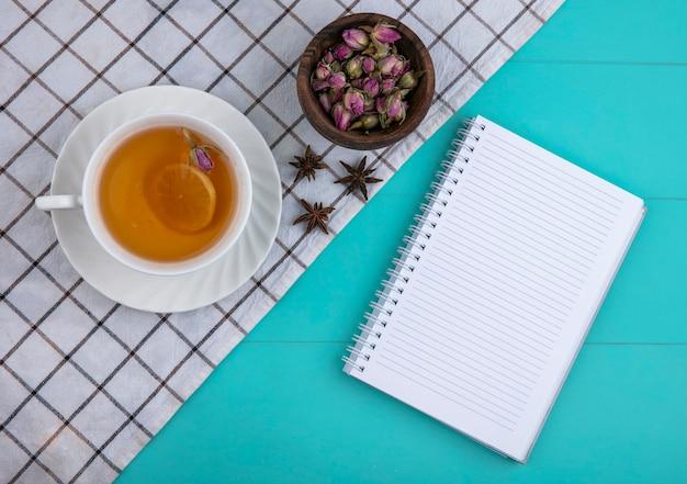 Draufsicht kopieren raum tasse tee mit einer zitronenscheibe und einem notizbuch mit getrockneten blumen auf einem hellblauen hintergrund Kostenlose Fotos