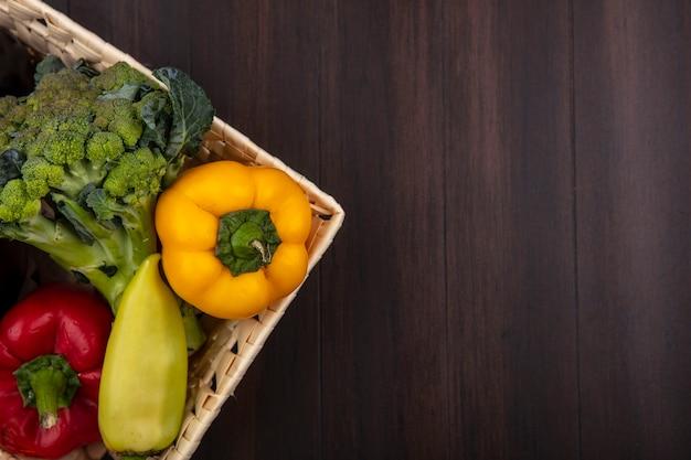 Draufsicht kopieren raumbrokkoli mit paprika im korb auf hölzernem hintergrund Kostenlose Fotos