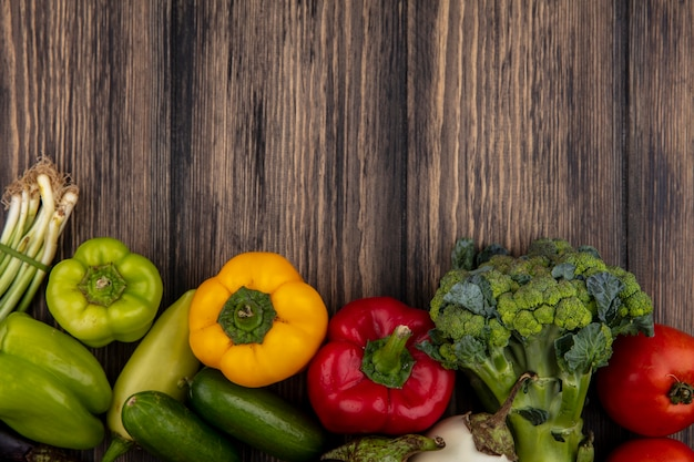 Draufsicht kopieren raumgurken mit farbigem paprikabrokkoli und tomaten auf hölzernem hintergrund Kostenlose Fotos