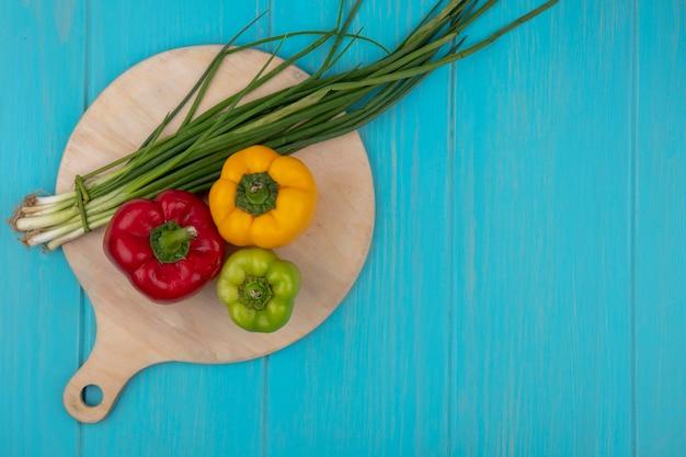 Draufsicht kopieren raumzwiebeln auf einem schneidebrett mit grüngelbem und rotem paprika auf einem türkisfarbenen hintergrund Kostenlose Fotos